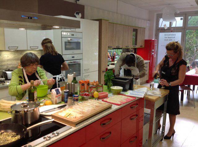 Teilnehmer kochen beim Nachbarschafts-Kochevent von DOCHOWs Küchen mit Geschmack in Berlin