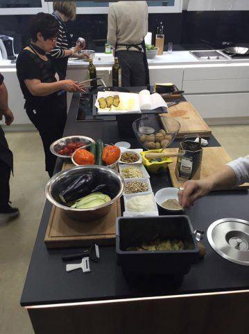 Teilnehmer bereiten das Essen zu beim Kochevent von DOCHOWs Küchen mit Geschmack in Berlin