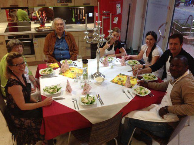 Teilnehmer essen beim Nachbarschafts-Kochevent von DOCHOWs Küchen mit Geschmack in Berlin