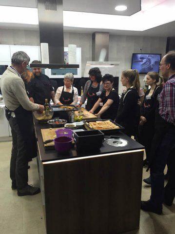 Teilnehmer des Kochevents stehen um die Kochinsel bei DOCHOWs Küchen mit Geschmack in Berlin