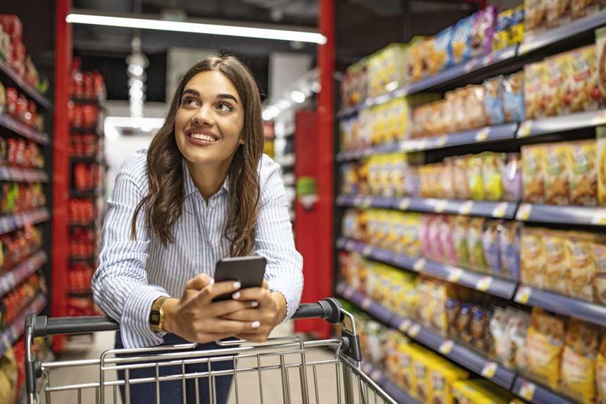 Frau schaut über ihr Handy im Kühlschrank nach fehlenden Zutaten
